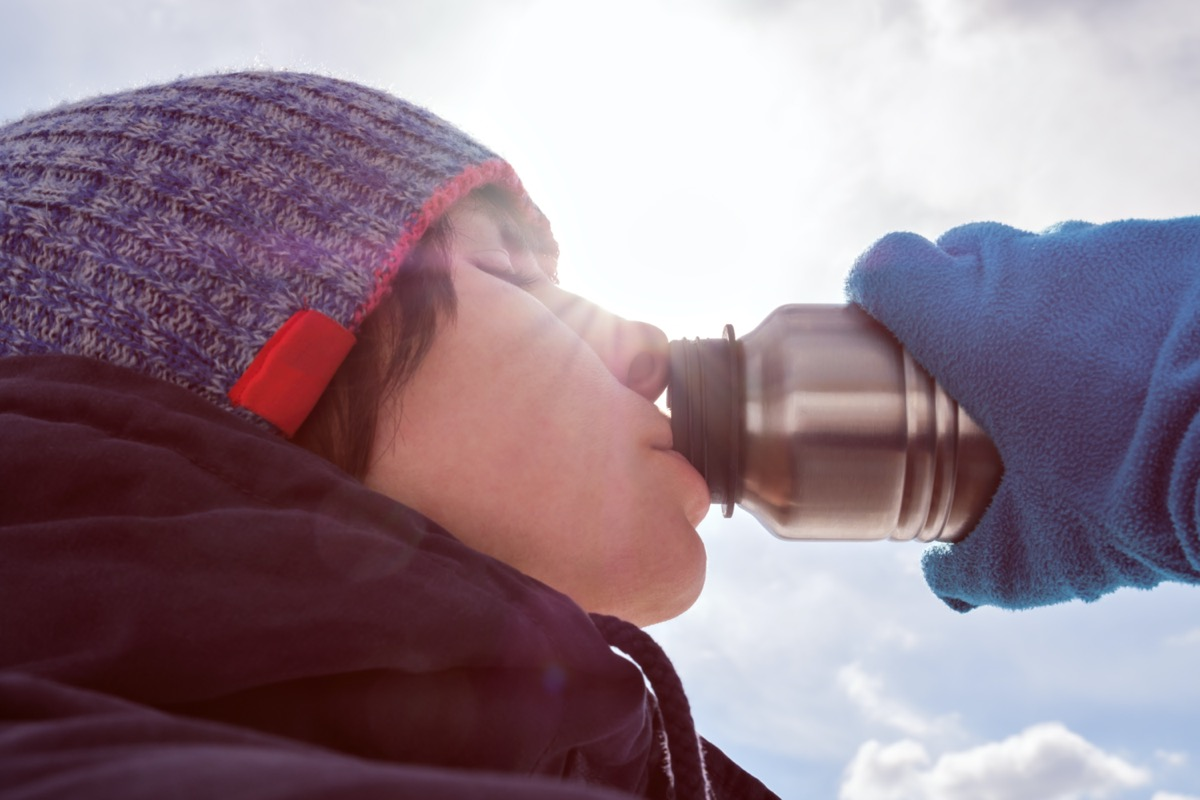 winter clothes eagerly drinks water from a bottle