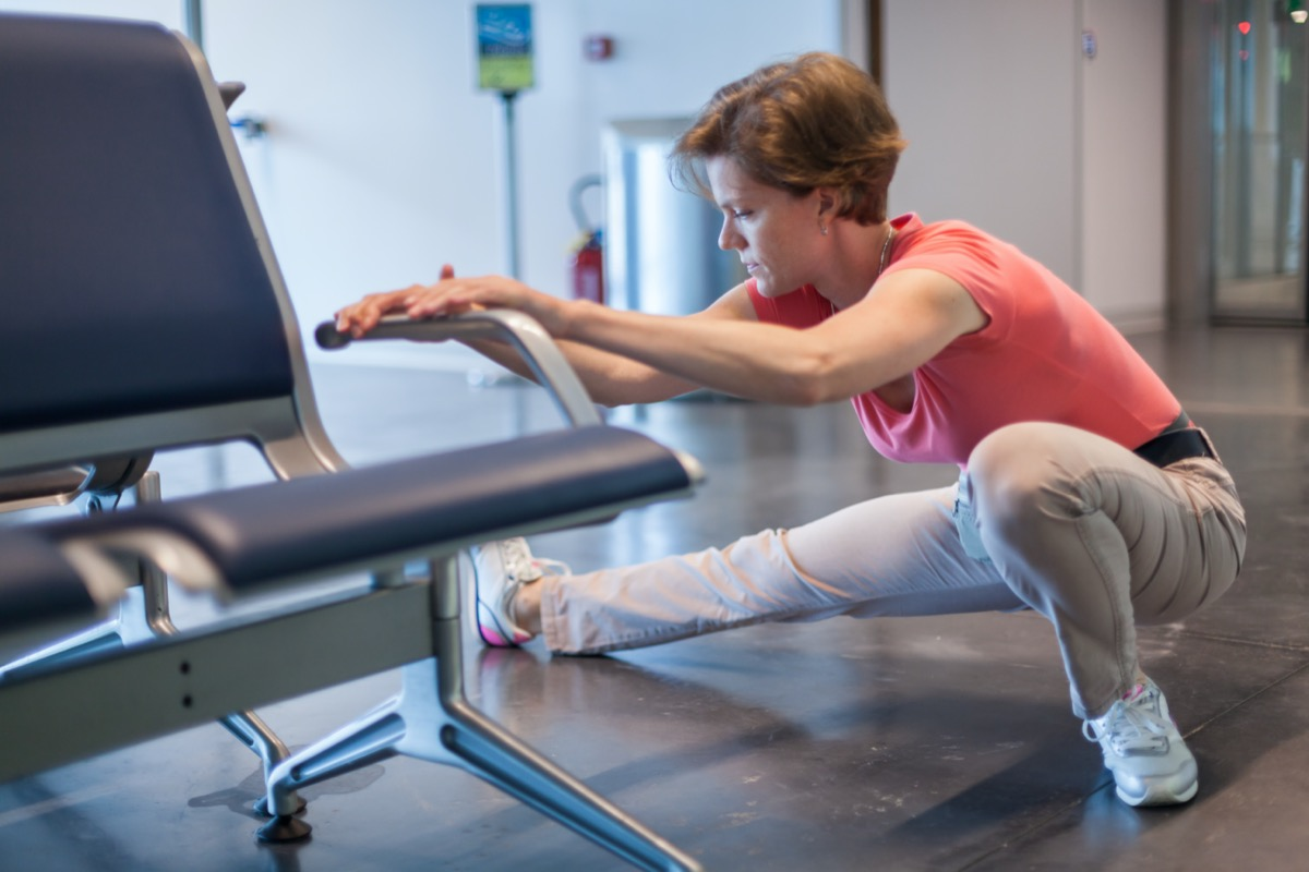 woman doing exercises in the airport hall while waiting for the plane