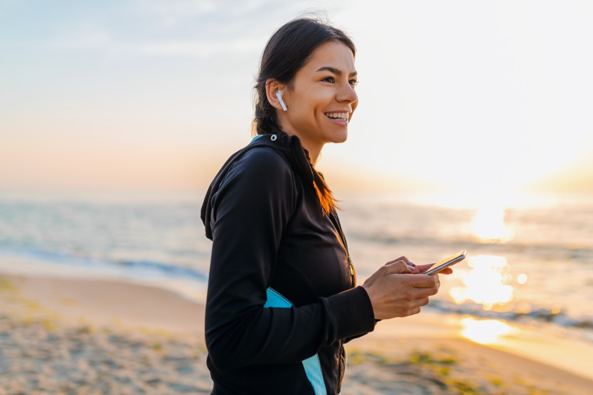 woman doing sport exercises on morning sunrise beach in sports wear, healthy lifestyle, listening to music on wireless earphones holding smartphone, smiling happy