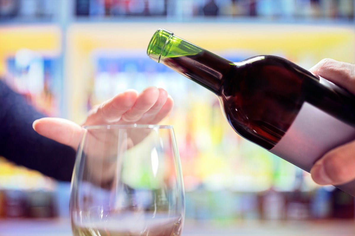 Woman refusing more alcohol from wine bottle in bar