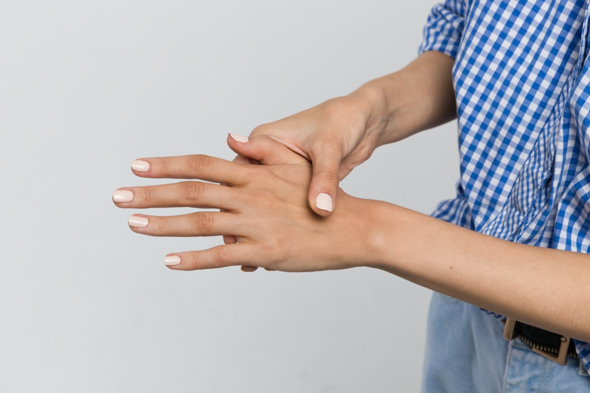 Close-up shot of woman suffering from pain in arms, weakness and kneads the hand/osteoarthritis, rheumatoid arthritis, wrist sprain, carpal tunnel syndrome, fractures