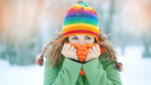 woman in snow with scarf on her face trying to warm herself
