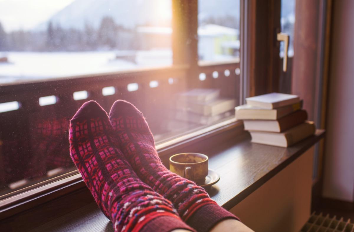 Feet in woollen socks by the mountains view
