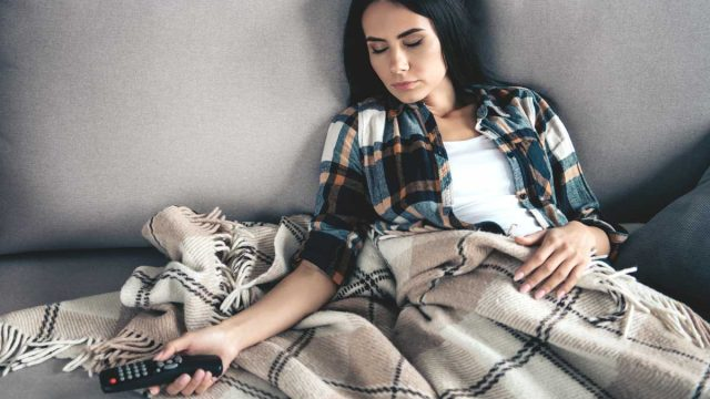 Young woman sleeping passed out on couch after watching tv with a food coma