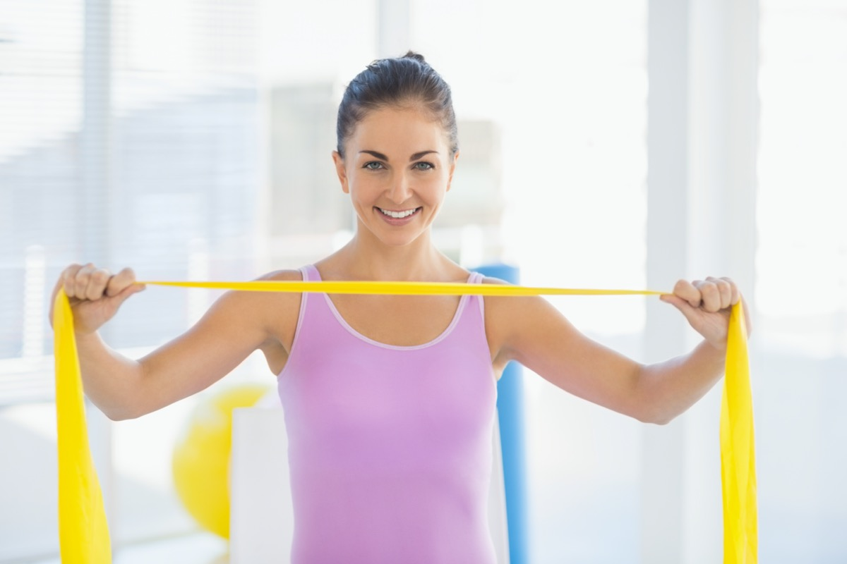 smiling woman holding resistance band at fitness studio
