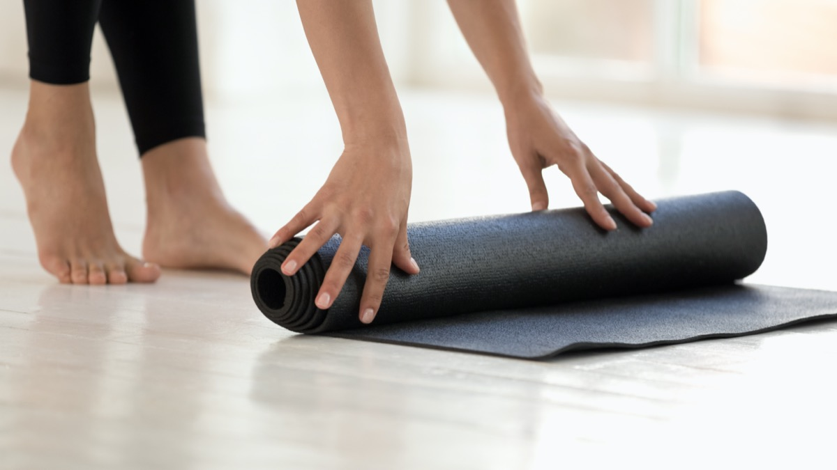 Woman wearing black leggings finished or starting workout rolling mat