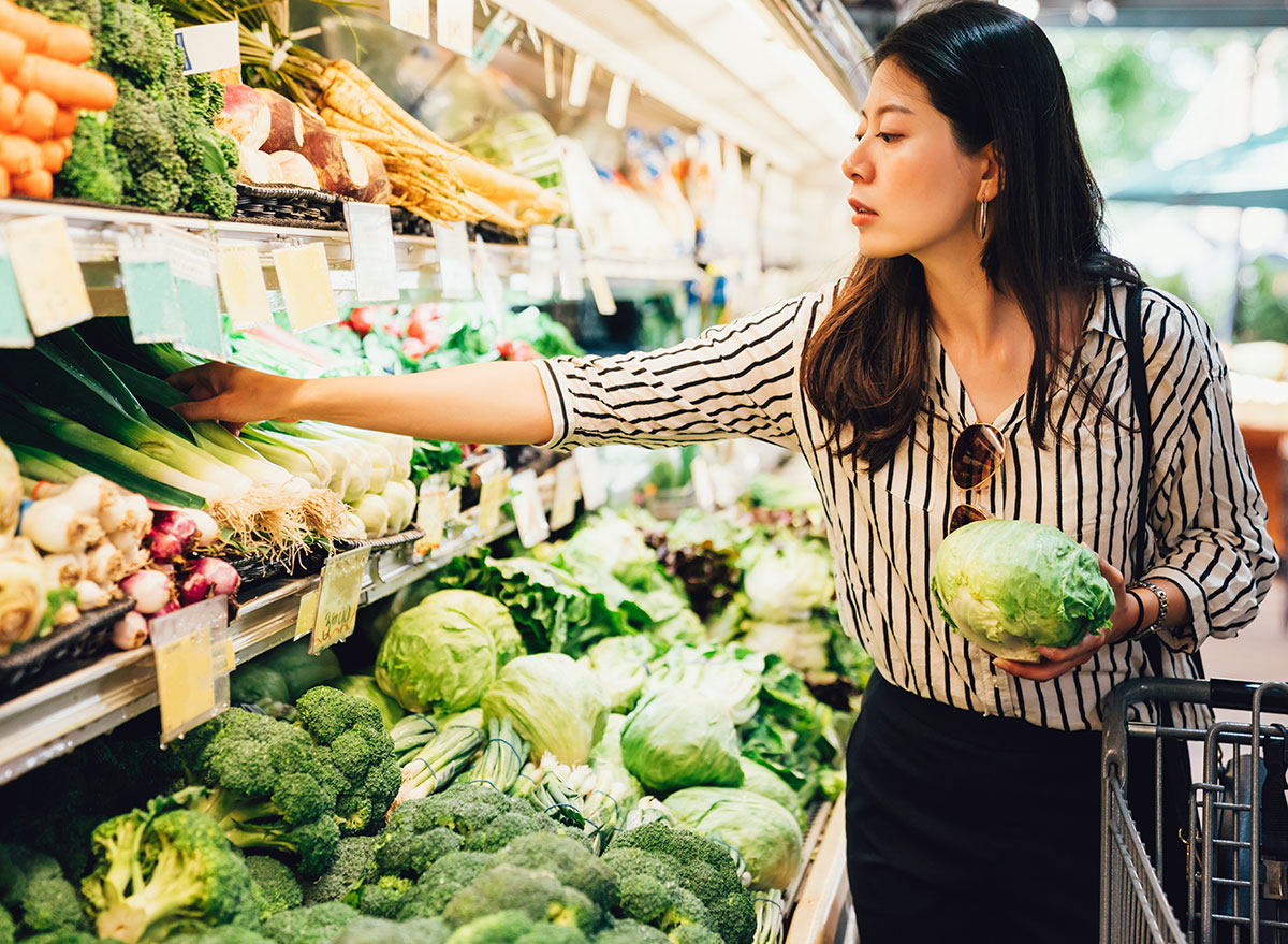 Woman holding lettuce and grabbing more produce at the grocery store