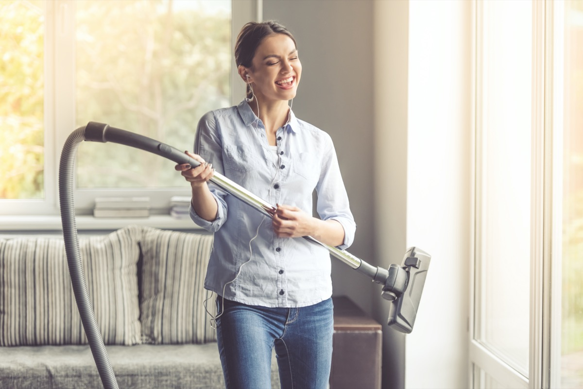 woman in earphones is imitating playing guitar using a vacuum cleaner and smiling while cleaning her house