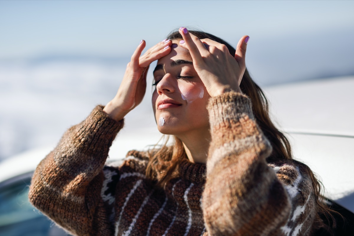 woman applying sunscreen on her face in snowy mountains in winter