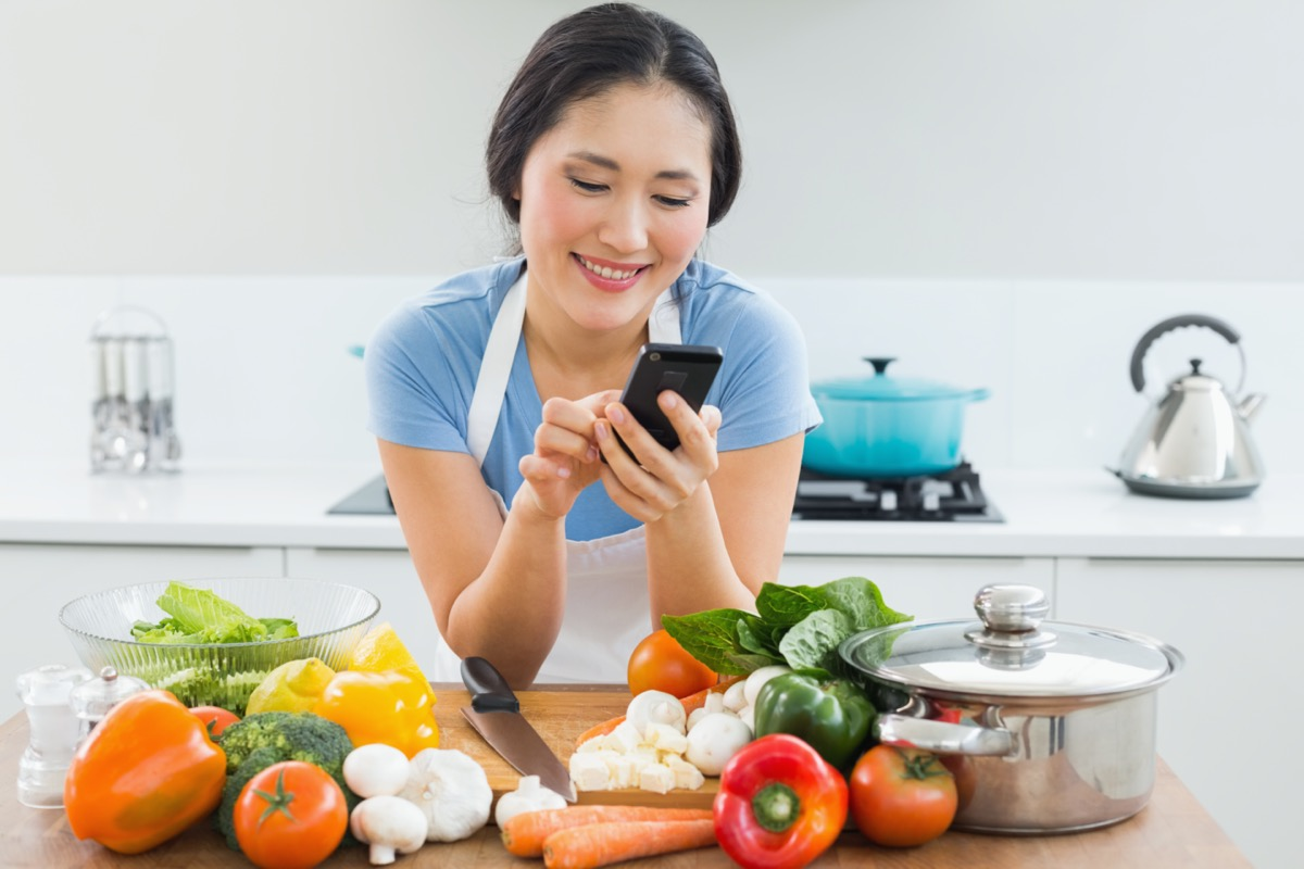 man text messaging in front of vegetables in the kitchen at home