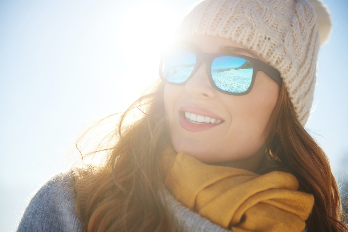 cheerful woman wearing shades enjoying sun in winter