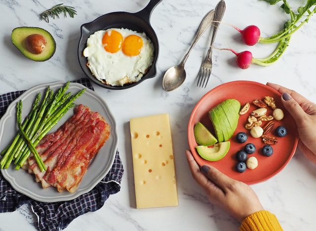 Woman holding plate of keto foods at a table