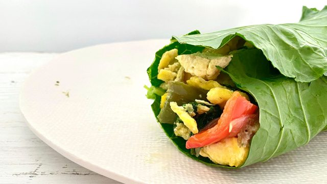 whole30 breakfast burrito on a white plate wrapped in a collard green