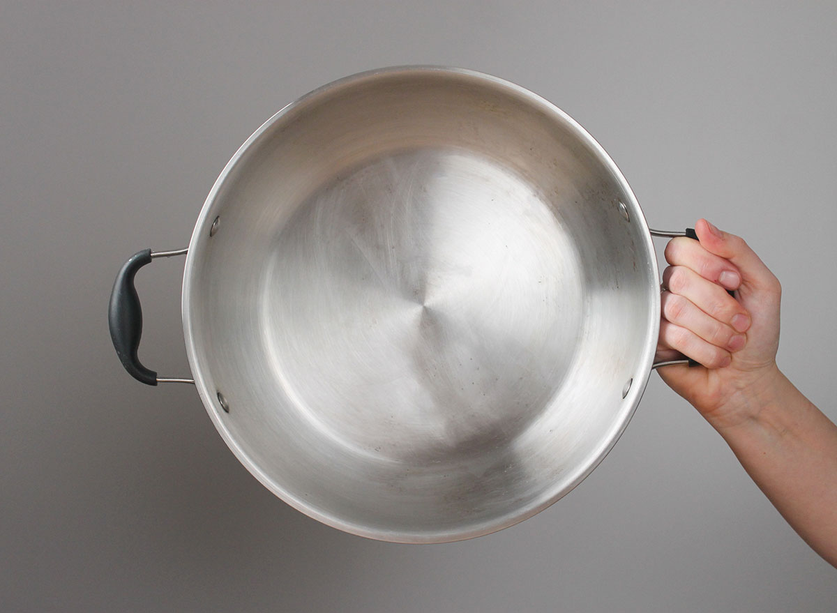 hand holding a clean pot against a grey background