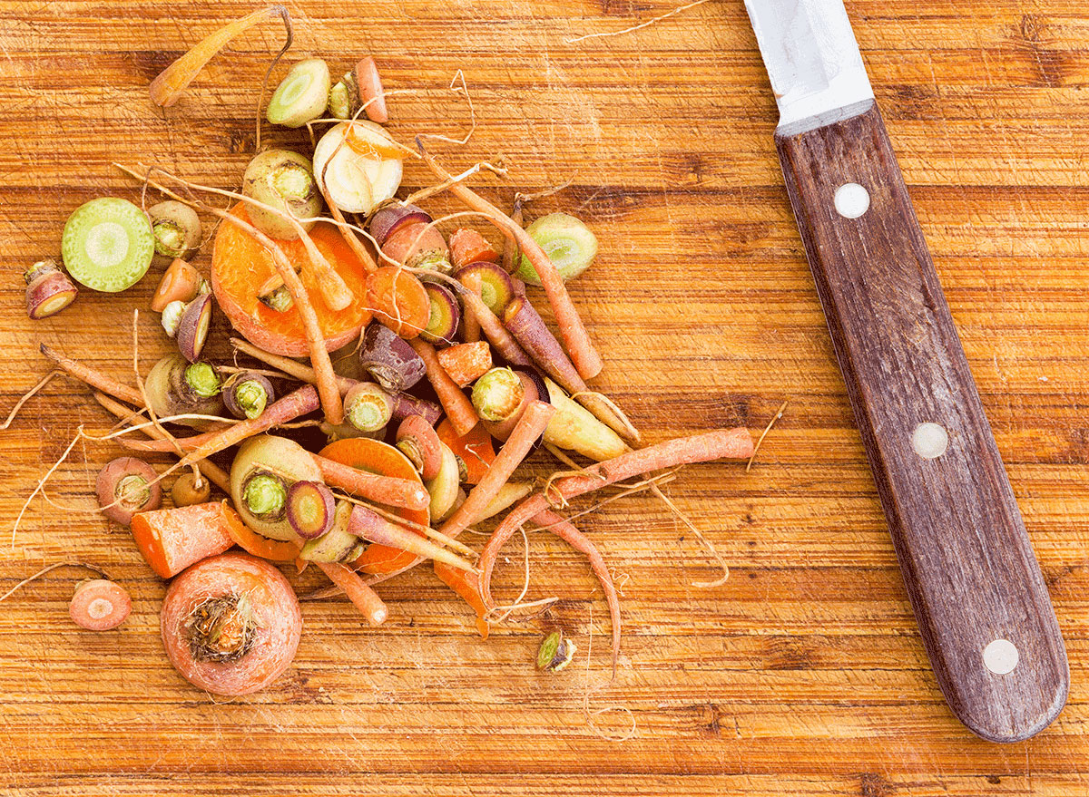 carrot scraps on cutting board with knife