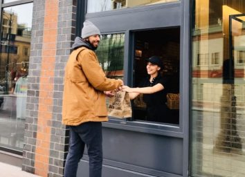 a man ordering a burrito or possibly a burrito bowl at a chipotle walk-through window