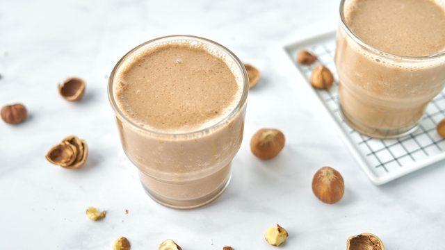 chocolate hazelnut smoothie in two glasses with hazelnuts around