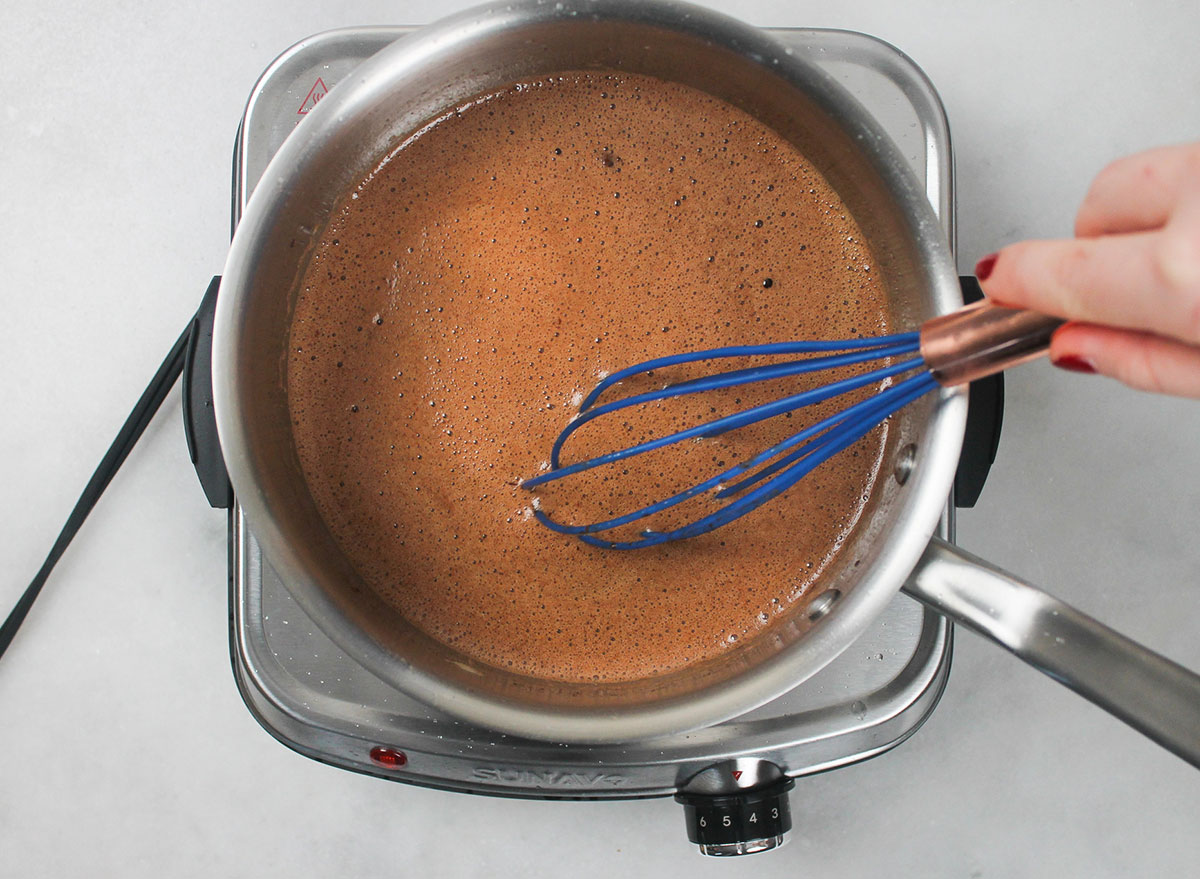 whisking together ingredients for coca cola cake in a pot on the stove