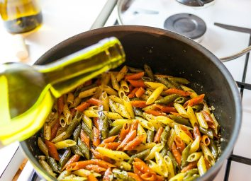 adding white wine in a skillet with homemade pasta
