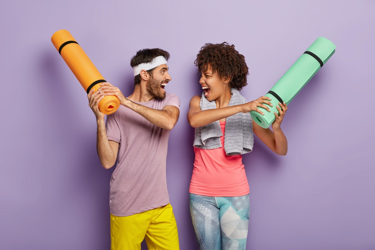 woman and man have fun in gym, fight with rolled up karemats, wear sport clothes, look at each other happily and shout loudly, have regular training together