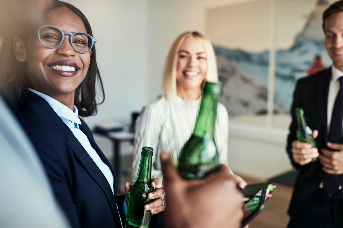 African American businesswoman talking and having drinks with a diverse group of colleagues in an office after work