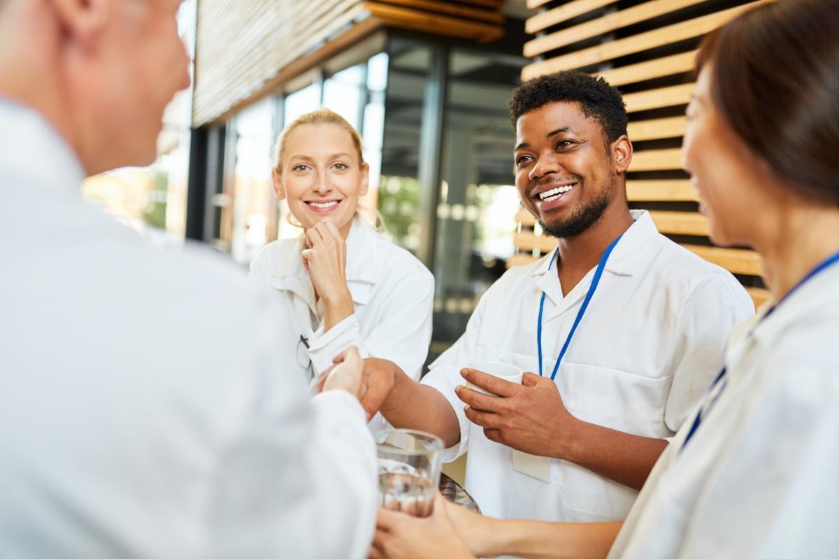 student welcomes senior doctor with handshake in coffee break