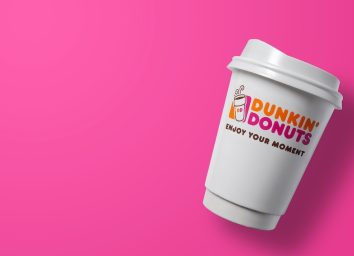 a dunkin donuts cup against a pink background