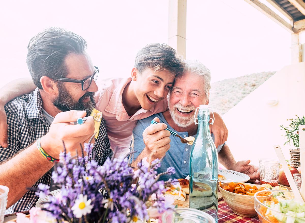 family hugging, laughing outside dinner