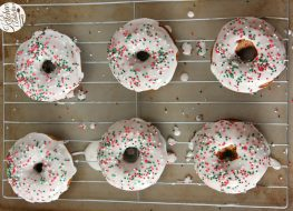 gingerbread donuts with icing and sprinkles on cooling rack