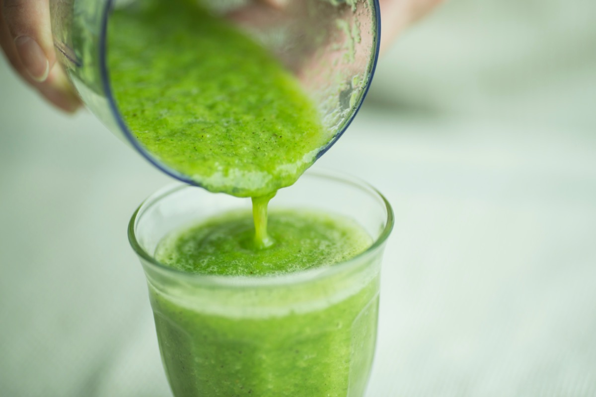 Woman to make a green smoothie in the mixer