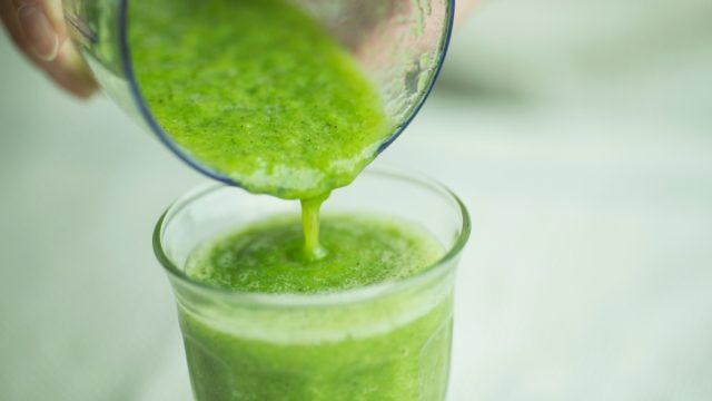 green smoothie being poured from blender into glass