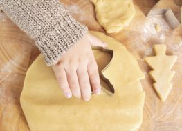 a hand pushing an angel cookie cutter into cookie dough to make baby yoda cookies