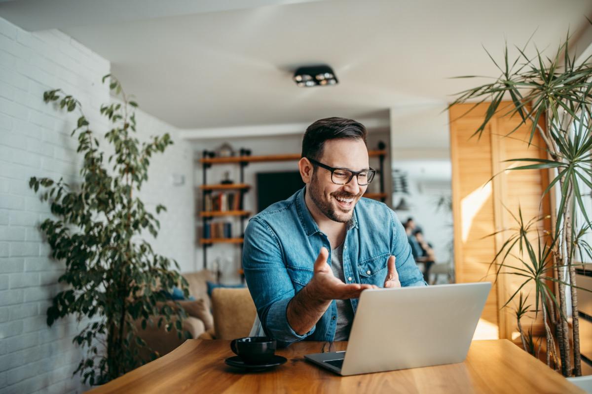 cheerful man having video call on laptop computer