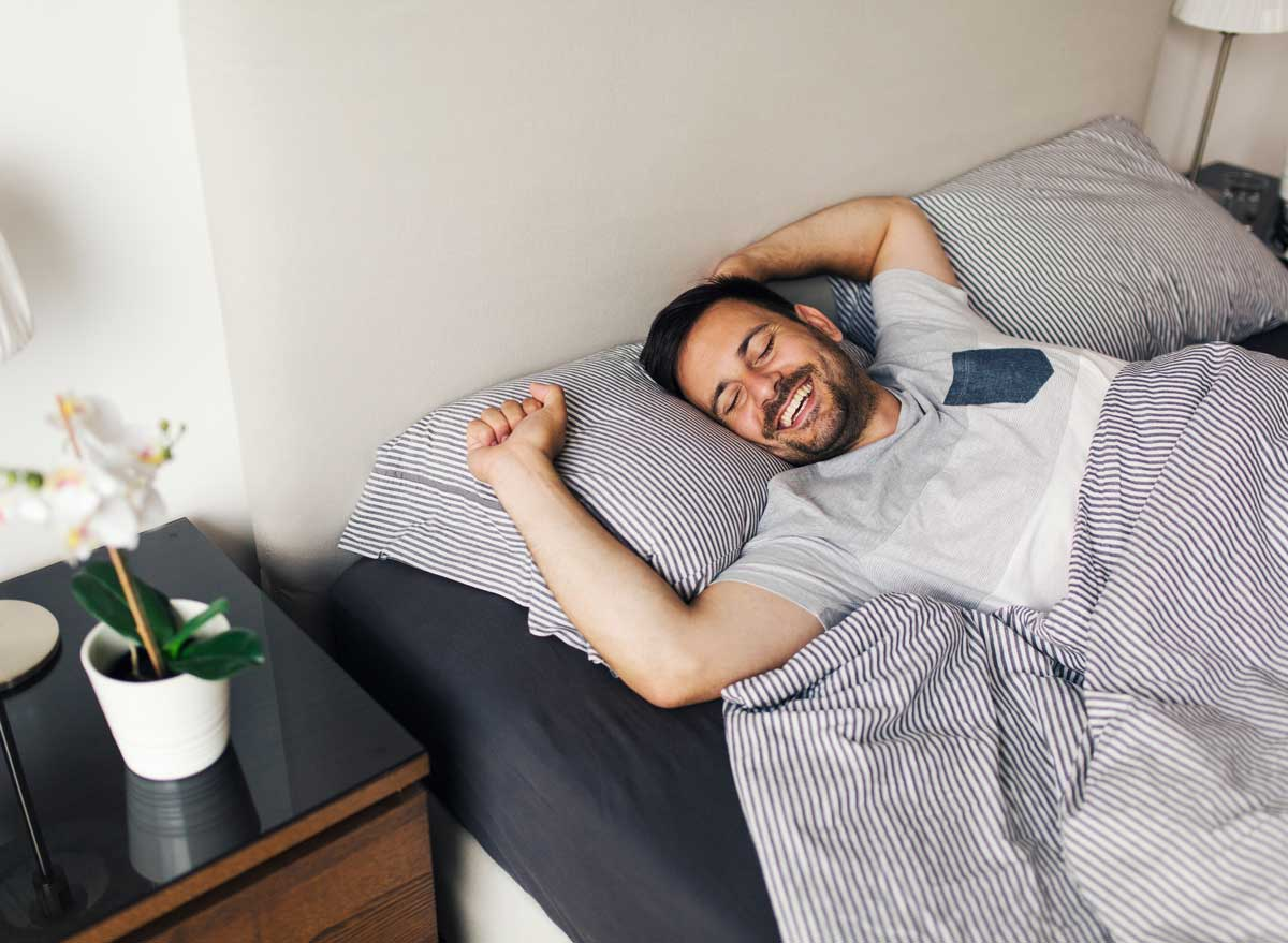 Happy man waking up from sleep in bed