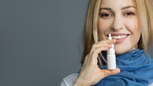 smiling girl in blue scarf holding nasal spray