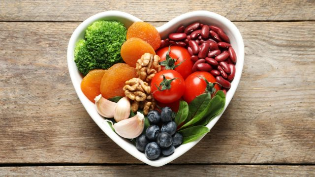 Bowl with products for heart-healthy diet on wooden background