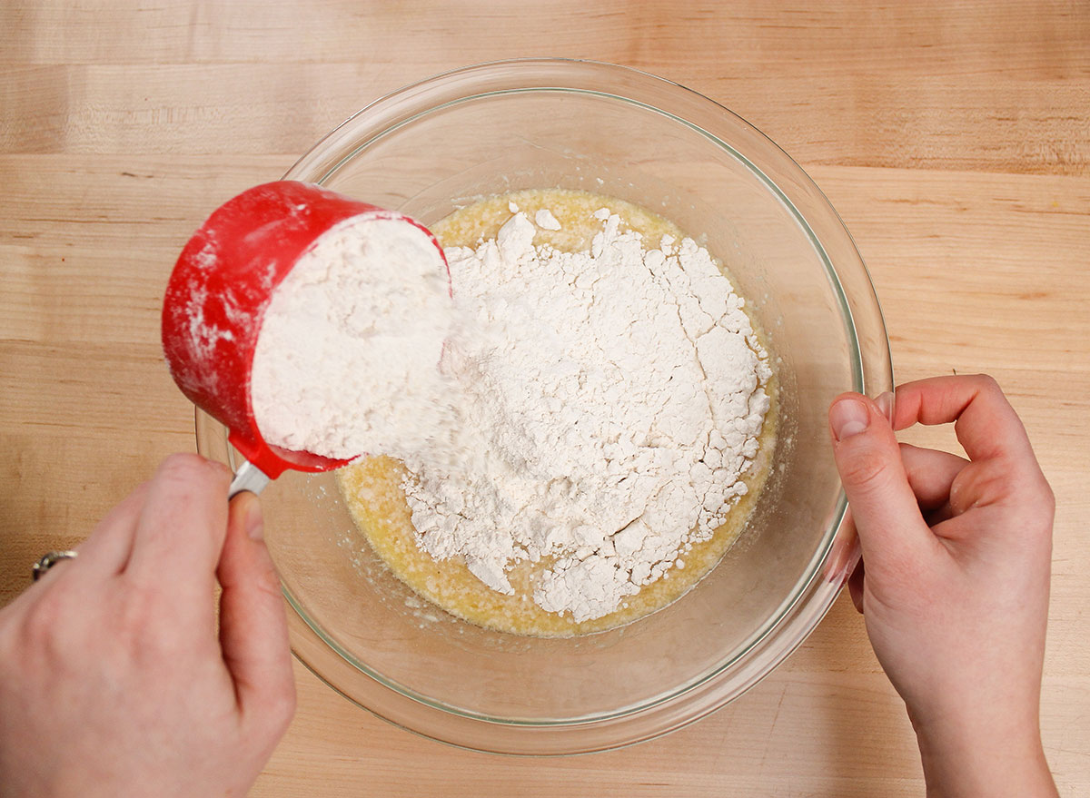 sprinkling flour and salt into wet yeast mixture for donuts