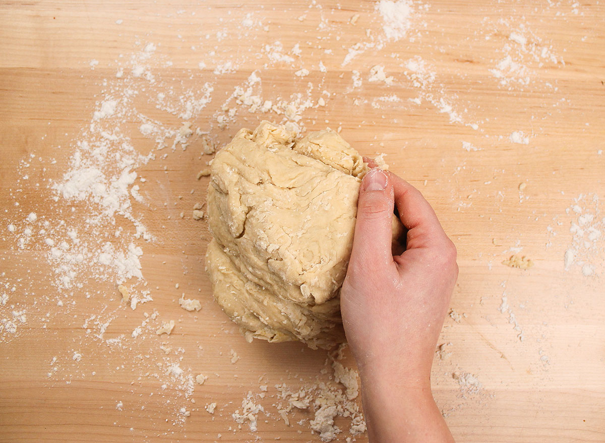 kneading donut dough on a floured surface
