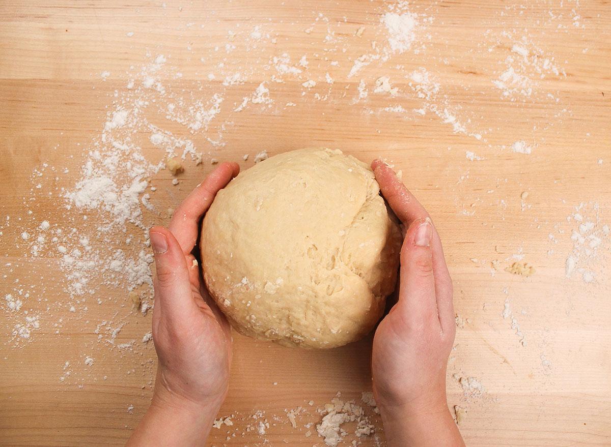 shaping a dough ball on a floured surface