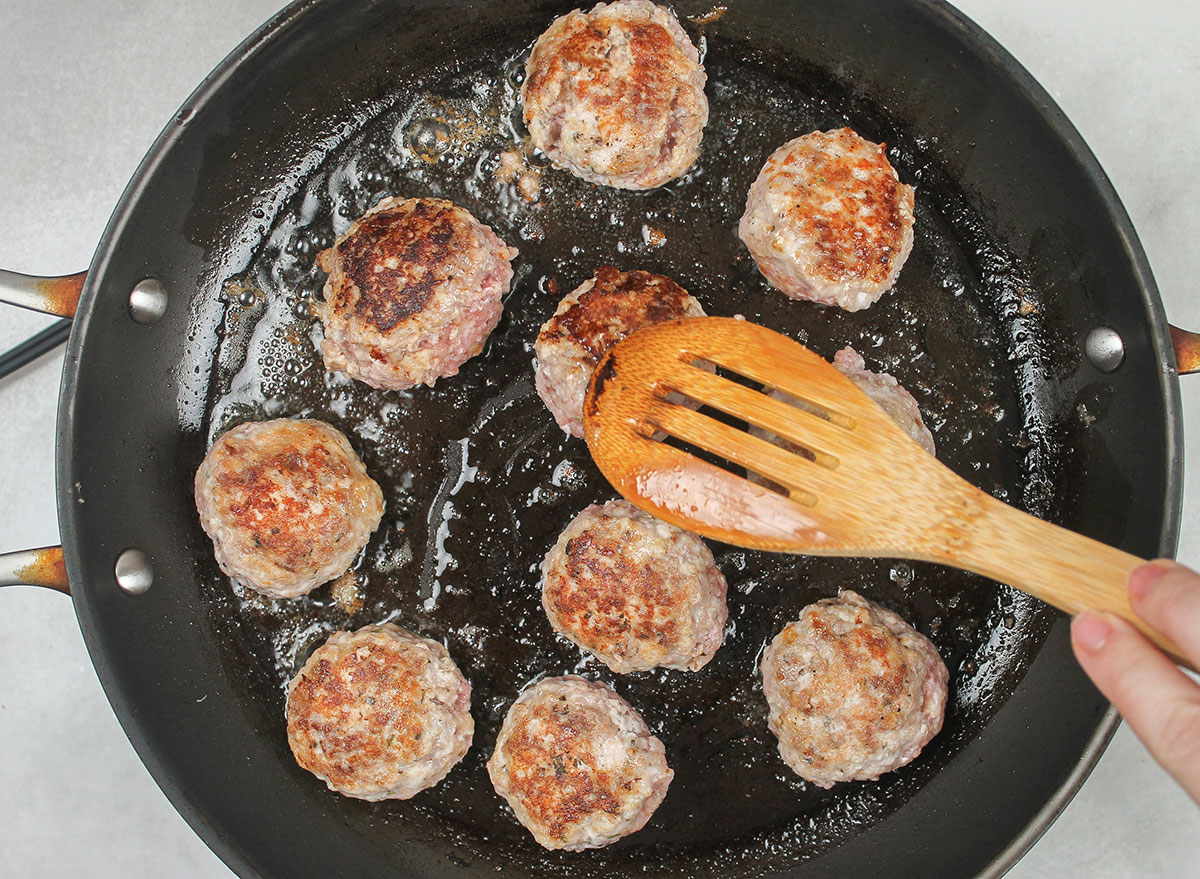 pan searing meatballs on a skillet