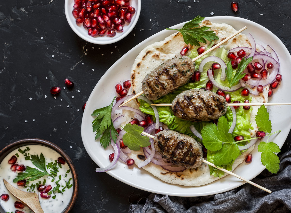 lamb kebabs on a plate with pomegranate seeds and fresh veggies