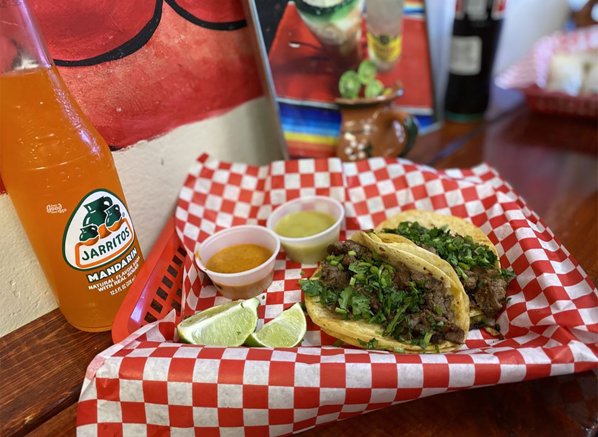 tacos and lime wedges with jarritos soda bottle