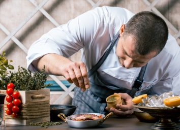 Chef sprinkling spices on dish in kitchen