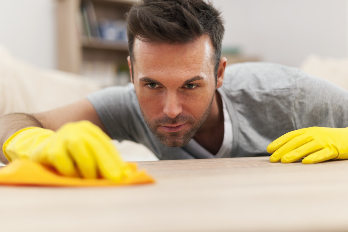 man cleaning stains off the table