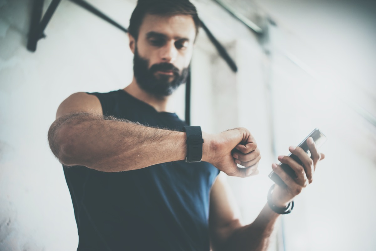 Bearded Sportive Man After Workout Session Checks Fitness Results Smartphone