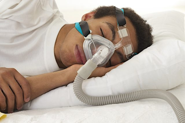 man sleeping with apnea and CPAP machine