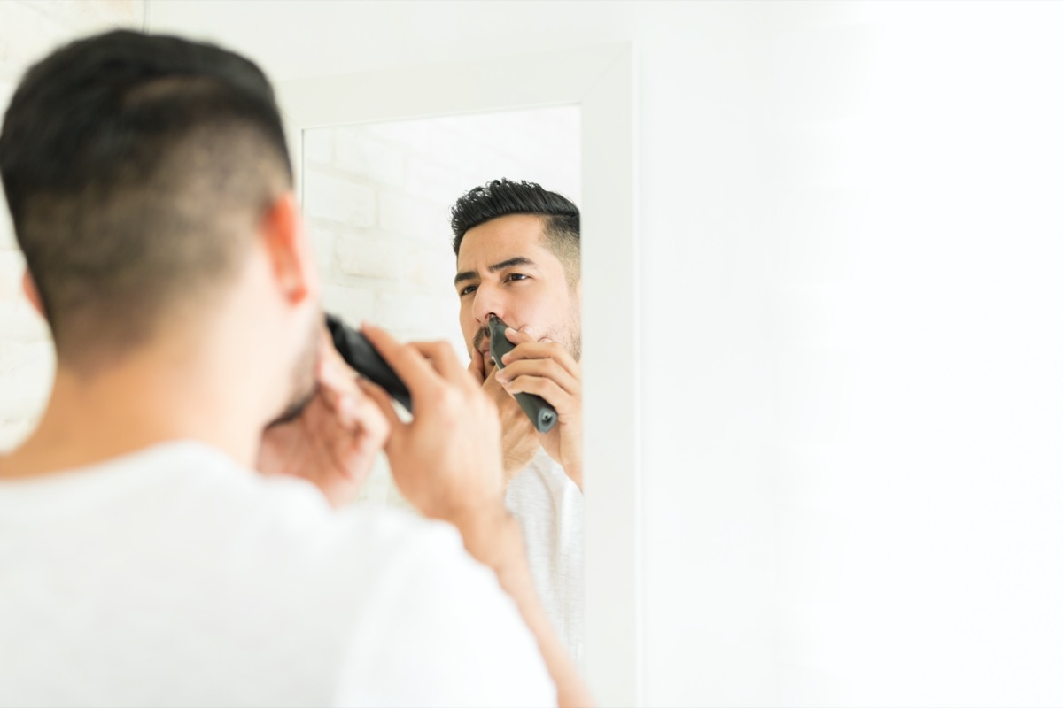 Reflection of man cutting his nasal hair with trimmer in bathroom