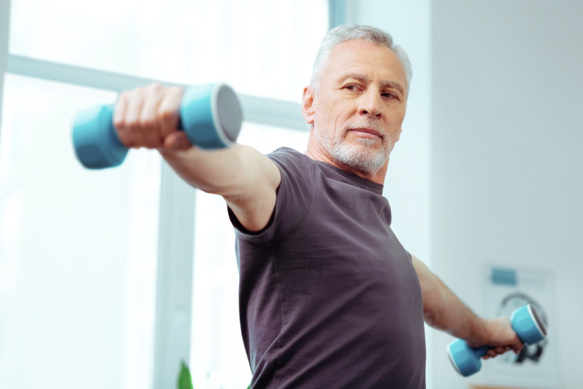 Strong fit aged man looking at his hand while training with dumbbells
