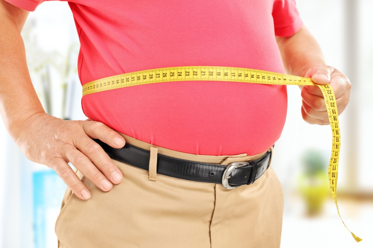 man measuring his belly at home.
