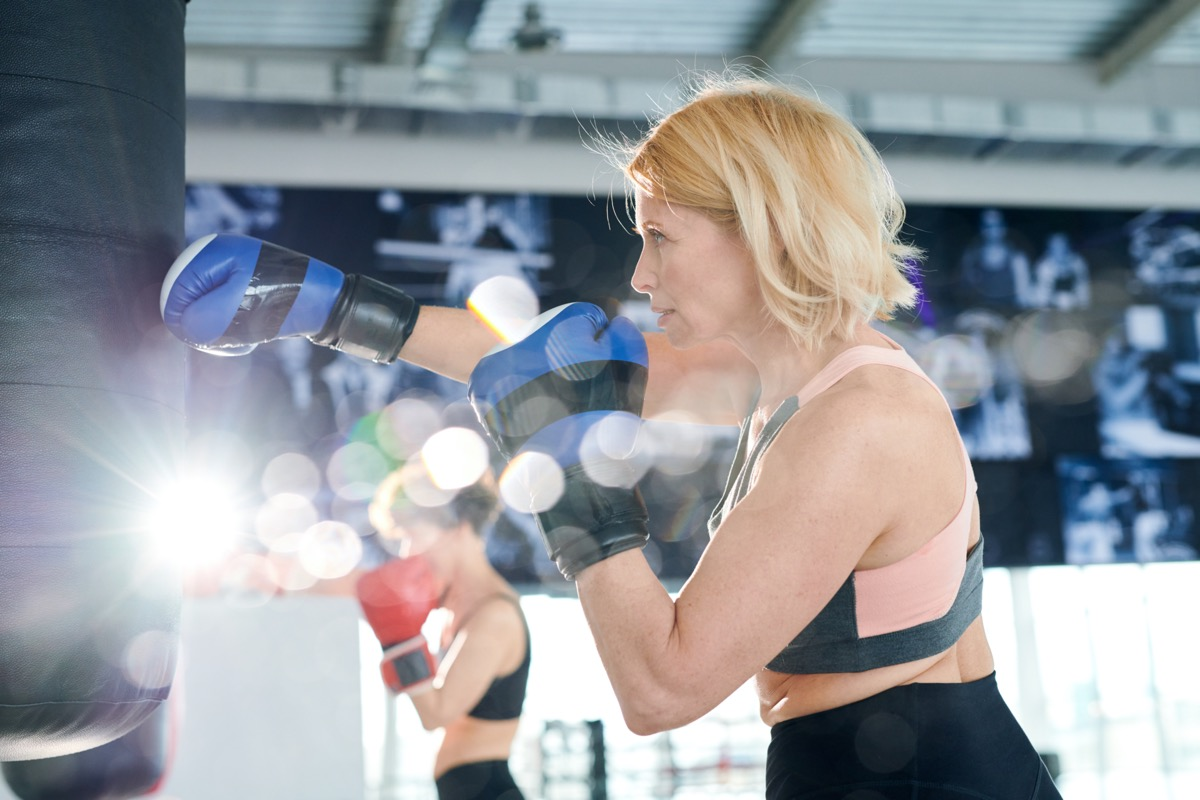 Active sportswoman in boxing gloves hitting punchbag while training in gym or contemporary leisure center